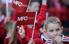 Young boy waving an MFC Foundation flag