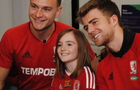 Ben Gibson and Patrick Bamford smile for a photo with a young girl