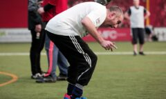A participant balances the football on his neck
