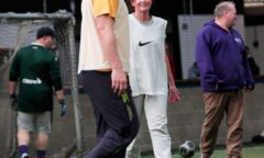 A man and a woman look at each other playing football