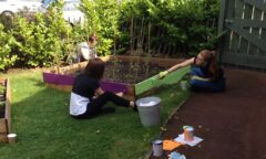 Two girls painting outdoor furniture