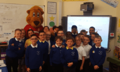 Roary and a class of children pose for a photo