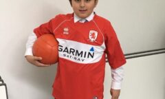 A pupil in Middlesbrough shirt holds a ball under his arm