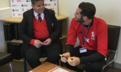 Stepping Up coach help a pupil with their learning