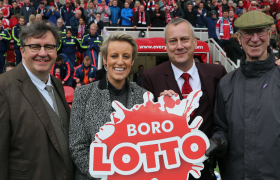 Mark Benton, Steph McGovern, Stephen Tompkinson and Jack Charlton pose with the Boro Lotto sign on match day