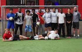 Refugee group line up for a photo in a football goal