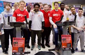 Marten de Roon & Viktor Fischer sitting on exercise bikes alongside participants on the PL Works programme