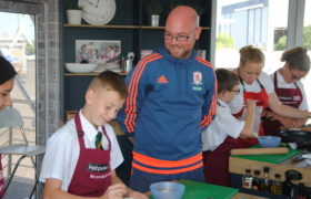 Foundation staff member engaging with a pupil while cooking