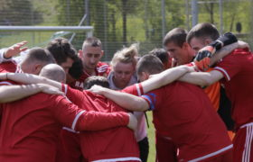 Participants in Middlesbrough FC kits huddle up for a team talk
