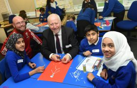 Foundation staff member smiling with local MP and three school pupils as they take part in some arts and crafts.