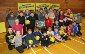 George Friend and a Foundation staff member pose for a photo with a group of children in a sports hall