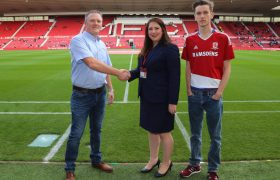 Man and Foundation staff member shaking hands pitchside
