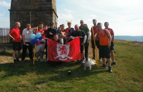 Young people and staff hold a Middlesbrough flag on top of Captain Cook's Monument