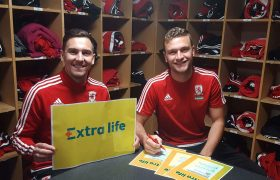 Stewart Downing and Ben Gibson pose with a yellow Extra Life poster in the club kit room